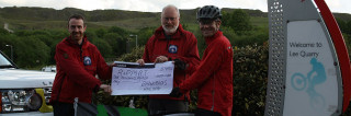 Chris Smith presenting the cheque to the team at the entrance to the quarry