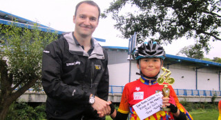 British Cycling NW Development Manager Alex Scoular presenting Tosh with his award