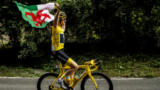 Geraint Thomas riding with the Welsh Flag on the final stage of the 2018 Tour de France after a historic win.